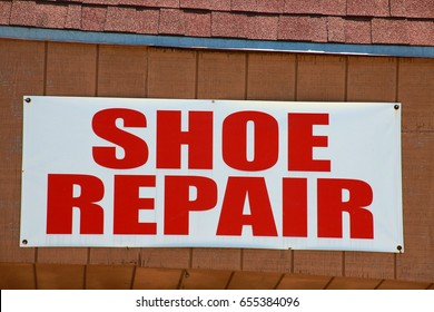 Shoe Repair Sign White with Red Letters Mounted under a Tiled Roof in a Shopping Center in a Sunny Afternoon