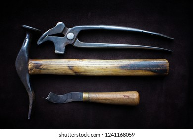 Shoe tools tongs hammer and legs that lie on a black cloth