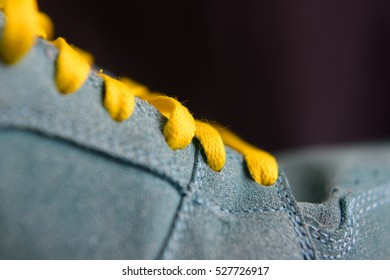 shoelace, running symbol, urban jogger, fitness concept, sport concept, sport symbol, yellow and blue, colored photography. dark background.
