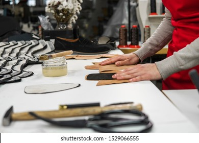 Shoemaker is adding glue with a brush to some pieces of leather that will be used to make shoes. The cobbler is working on his desk in his workshop.