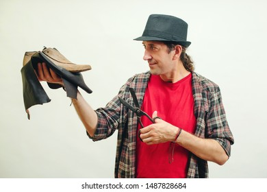 Shoemaker modeling mens shoe at his workshop. Small business concept. Handmade leather shoes. Cobbler holding set of tools and leather