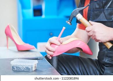 Shoemaker repair female spike shoe. Hammering tip on heel