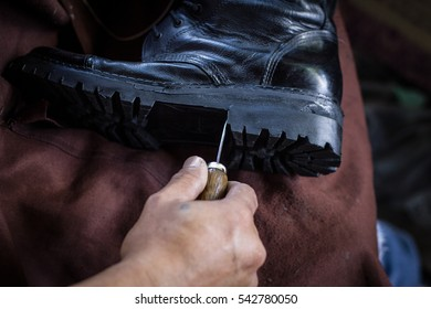 Shoemaker is repairing shoe