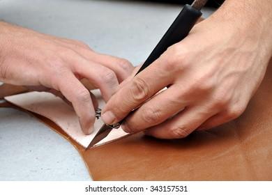 Shoemaker is repairing shoe. Shoemaker sews shoes. Shoemaker workshop. Shoemaker cutting leather in a workshop. Fashion designer shoes.