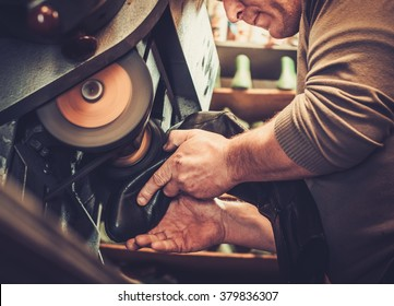 Shoemaker repairs shoes in the studio craft grinder machine.