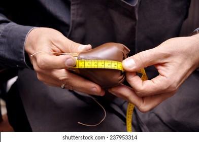 Shoemaker sews shoes. Shoemaker workshop.