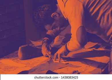 Shoemaker or shoe designer working with leather for the production of handmade shoes. Bitonal effect with two tones