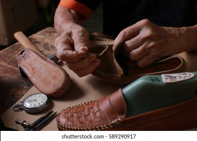 Shoemaker, stitching of a leather handmade shoe