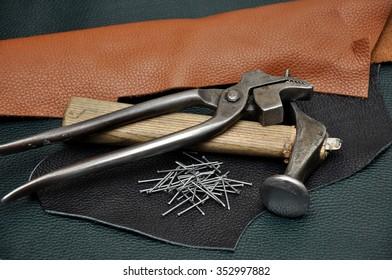 Shoemaker tools. Shoemaker workshop. The hammer of a shoemaker. Hammer shoemaking. The pieces of skin.