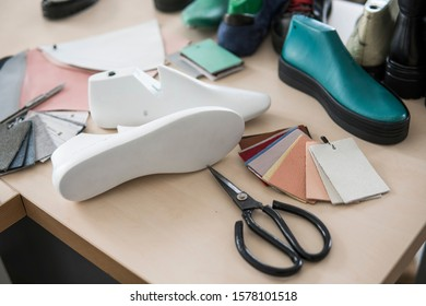 Shoemaker workplace with tools, shoes, leather and last.