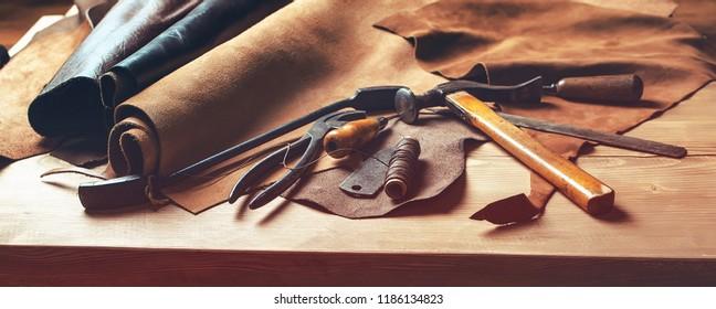 Schuhmacher-Arbeitstisch. Werkzeuge und Leder am Schuster Arbeitsplatz. Set von Lederwerkzeugen auf Holzhintergrund. Schuhmacherwerkzeuge auf Holztisch