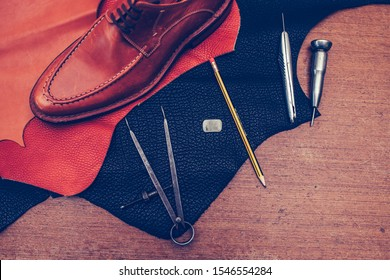 Shoemaker's work desk. Tools and leather at cobbler workplace. Man classic brown shoes and leather shoemaking tools and set of leather craft tools . Shoes maker tools on wooden table