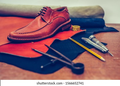 Shoemaker's work desk. Tools and leather at cobbler workplace. Man classic brown shoes and leather shoemaking tools and set of leather craft tools .  Selective focus and small depth of field.