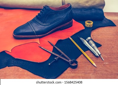 Shoemaker's work desk. Tools and leather at cobbler workplace. Man classic black shoes and leather shoemaking tools and set of leather craft tools . Shoes maker tools on wooden table