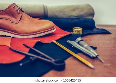 Shoemaker's work desk. Tools and leather at cobbler workplace. Man classic brown shoes and leather shoemaking tools and set of leather craft tools . Shoes maker tools on wooden table. Selective focus.