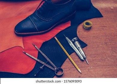 Shoemaker's work desk. Tools and leather at cobbler workplace. Man classic black shoes and leather shoemaking tools and set of leather craft tools . Shoes maker tools on wooden table. Selective focus