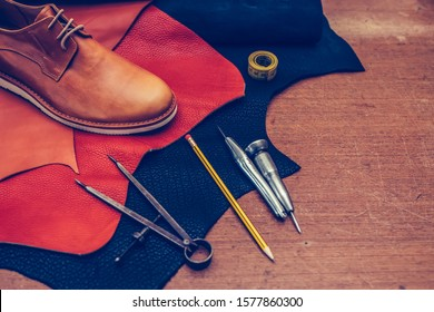 Shoemaker's work desk. Tools and leather at cobbler workplace. Man classic brown shoes and leather shoemaking tools and set of leather craft tools . Shoes maker tools on wooden table. Selective focus