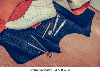Shoemaker's work desk. Tools and leather at cobbler workplace. Shoes, leather, shoemaking tools and set of leather craft tools . Shoes maker tools on wooden table. Selective focus