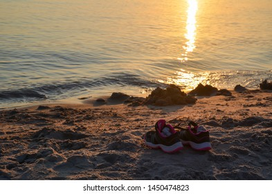 Shoes by seaside on a sandy beach with sunset reflections in the water