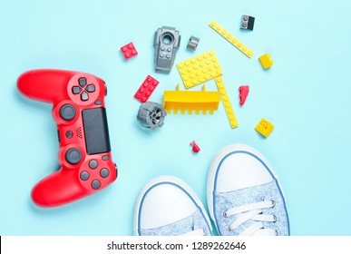 Shoes and children's 80s entertainment and toys on a blue background. Red gamepad, children's constructor bricks, sneakers, top view