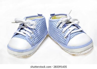 Shoes for cute little baby in blue on white fabric.