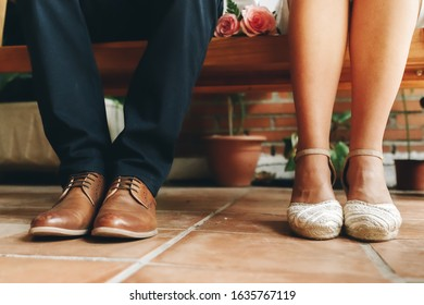 Shoes of groom and bride and her small wedding bouquet of pink roses sitting and waiting in a wooden bench. Wedding day concept.