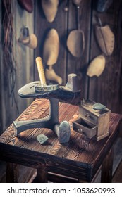 Shoes, hammer and nails in old cobbler workshop