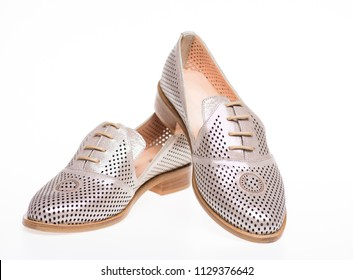 Shoes made out of silver leather on white background, isolated. Footwear for women on flat sole with perforation. Female footwear concept. Pair of fashionable comfortable loafer shoes.