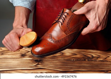 Shoes master (man) polishing leather shoes with brush