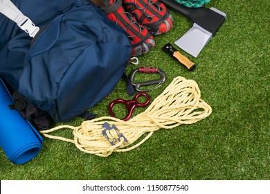 Shoes and objects for survival in adventure travel, on the green grass