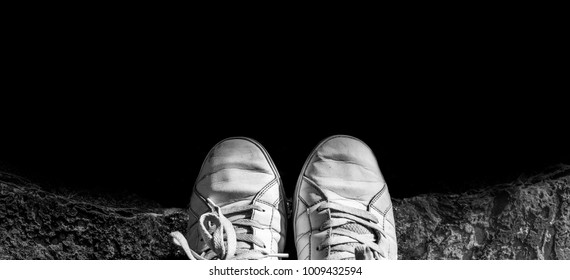 Shoes on the cliffs, deep down and fall into darkness.