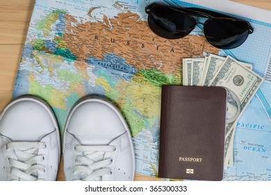 shoes, passport, cash, sunglasses on a map