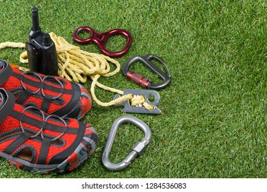 shoes and ropes for mountains are lying on the green grass