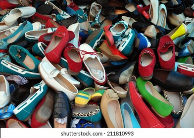 Shoes for sale at street market. Pile of assorted footwear abstract background.