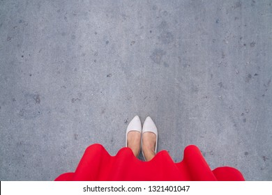 Shoes selfie from above. Feet shot in nude ballerina or beige heels and red long skirt on the ground. The lady wears simply shoe. (with copy space)