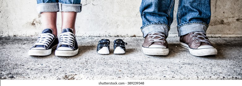 shoes and sneakers of parents and expected baby