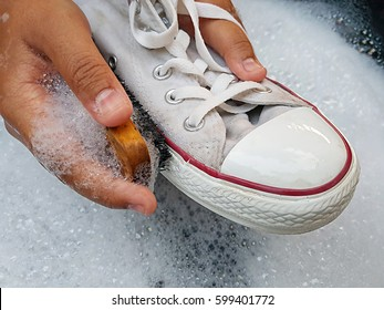 Shoes or sneakers in a wash basin with soapy water.washing the dirty sneakers, cleaning the shoes.