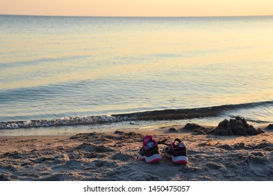 Shoes with socks by seaside on a beach by sunset