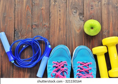 Shoes and sports equipment on wooden floor.