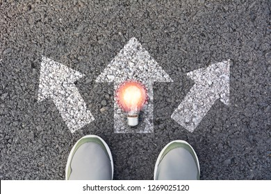 Shoes standing  and light bulb at the crossroad and get to decision which way to go. Ways to choose concept.