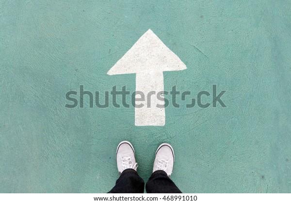 обувь, стоящая на бетонном полу, и белый знак направления идти вперед