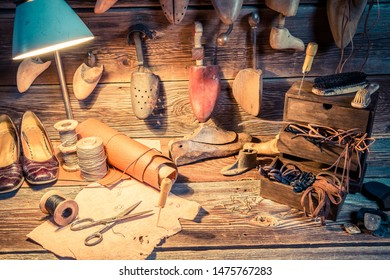 Shoes, tools and leather in rustic cobbler workshop