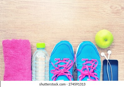 Shoes and water with set for sports activities on tiled floor.