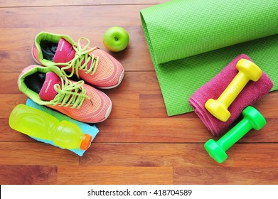 Shoes and water with set for sports activities on wooden floor.