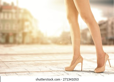 shoes and woman legs in city and sunset