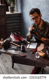 shoeshine guy sewing the sole of shoes, close up photo.