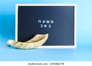 Shofar horn and chalkboard with  text Tisha B'Av written in hebrew. Shofar- Religious and Jewish Holidays symbol. Tisha B'Av day in Judaism, on which a number of disasters in Jewish history occurred.