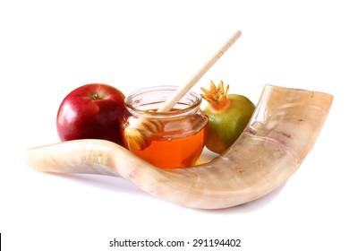 shofar (horn), honey, apple and pomegranate isolated on white. rosh hashanah (jewish holiday) concept . traditional holiday symbol.