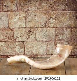 shofar (horn) on wooden table in front of jerusalem ancient wall. rosh hashanah (jewish holiday) concept . traditional holiday symbol.