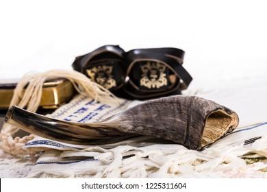 Shofar, tefillin, tallit and books on white background